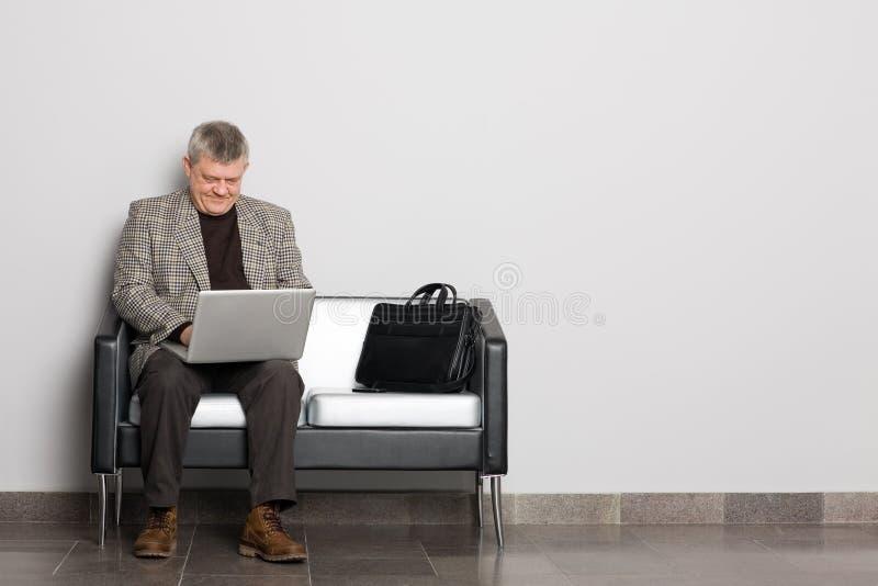 Uomo invecchiato centrale che per mezzo di un computer portatile fotografia stock libera da diritti