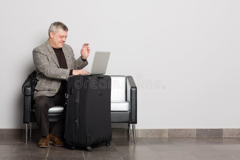 Uomo invecchiato centrale sorridente che per mezzo di un computer portatile fotografie stock libere da diritti