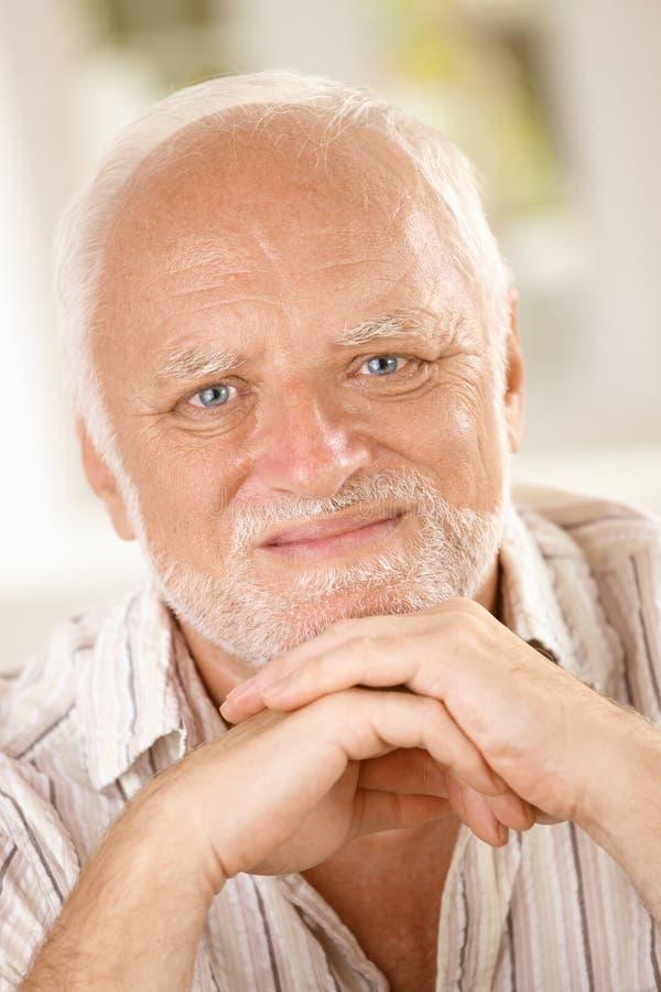 Uomo invecchiato che sorride alla macchina fotografica fotografia stock