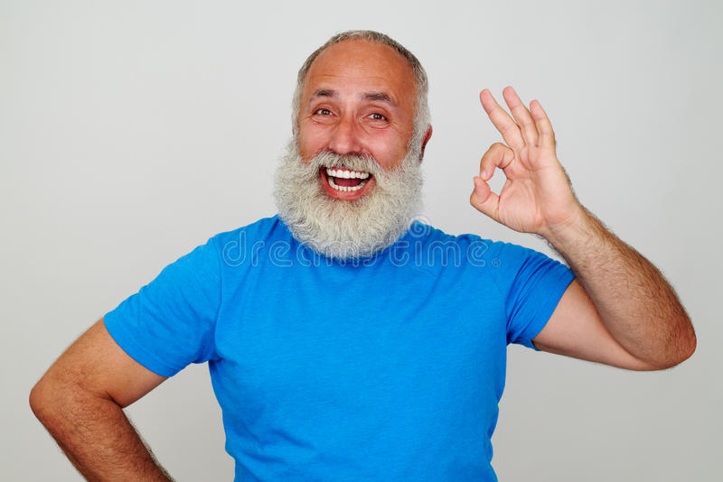 Uomo invecchiato con la barba bianca e vasto il sorriso che mostrano gesto GIUSTO fotografie stock libere da diritti