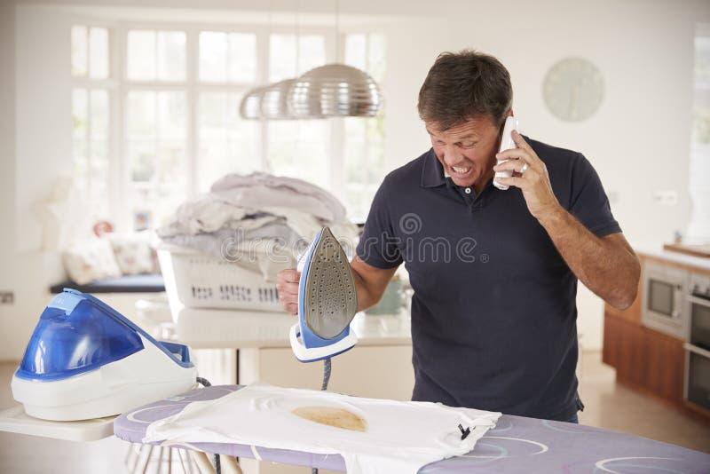 Uomo invecchiato mezzo distratto dal telefono quando rivestire di ferro brucia la camicia immagine stock
