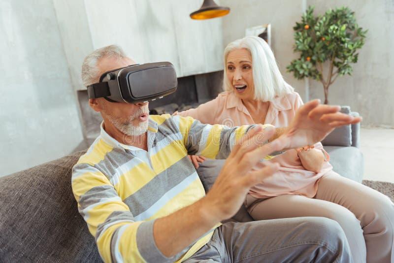 Uomo invecchiato piacevole che collauda il dispositivo di VR con la sua moglie positiva fotografia stock