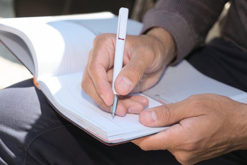 Uomo irriconoscibile che tiene una penna e una latteria fotografie stock