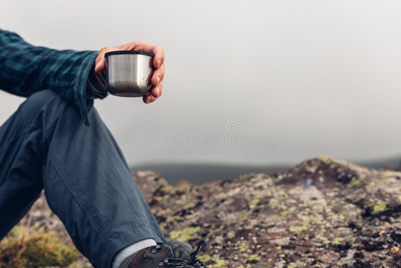 Uomo irriconoscibile della viandante che tiene tazza in sua mano Escursione dell'arrivo immagini stock