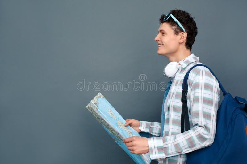Uomo isolato sul concetto grigio di turismo della parete che cammina con sorridere della mappa della tenuta dello zaino eccitato fotografia stock libera da diritti