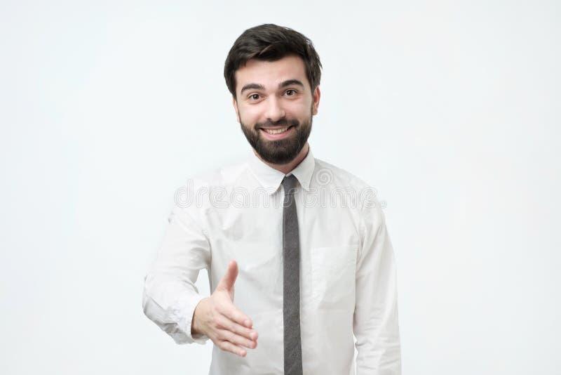 Uomo ispanico bello in camicia bianca che dice ciao, stringente mano immagine stock