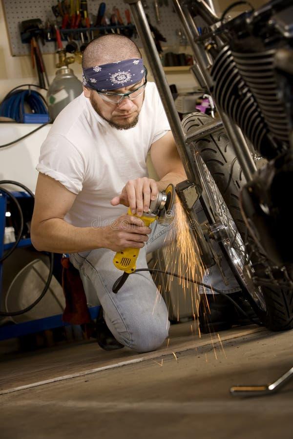 Uomo ispanico che usando smerigliatrice sul motociclo fotografie stock libere da diritti