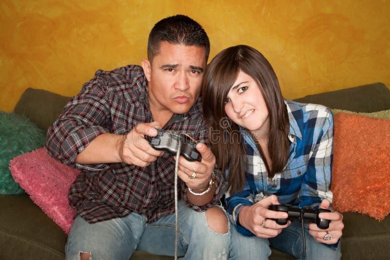 Uomo ispanico e ragazza che giocano video gioco immagine stock