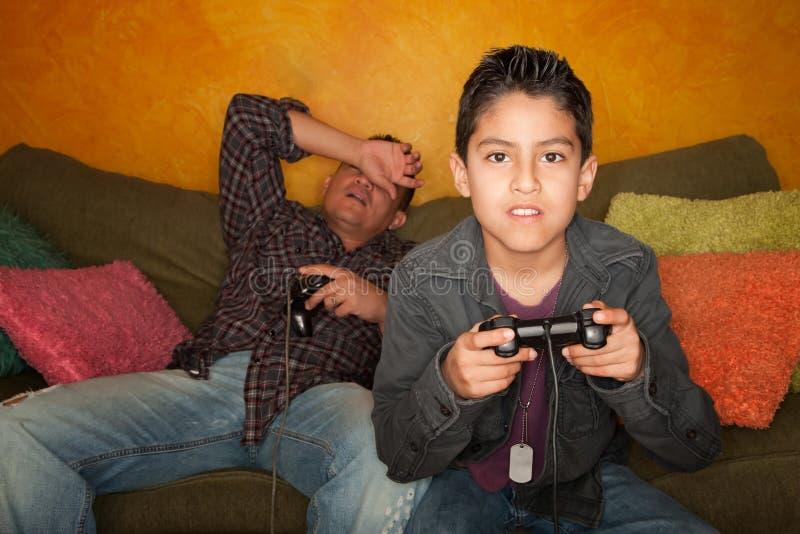 Uomo ispanico e ragazzo che giocano video gioco immagine stock libera da diritti