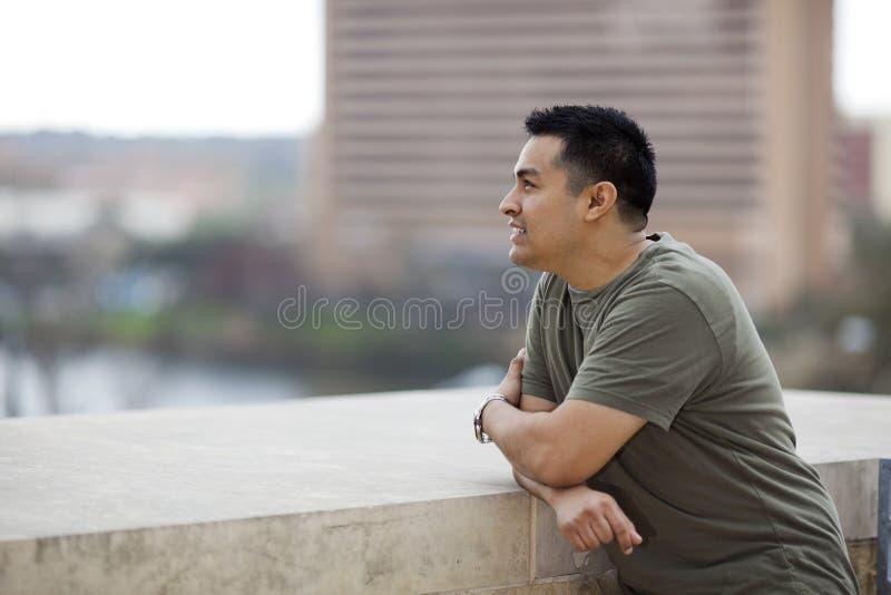 Uomo ispanico - osservando fuori dal balcone fotografie stock libere da diritti