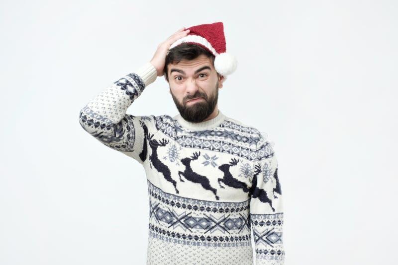 Uomo ispano in cappuccio rosso di natale che pensa profondamente ai regali, esaminanti macchina fotografica fotografia stock