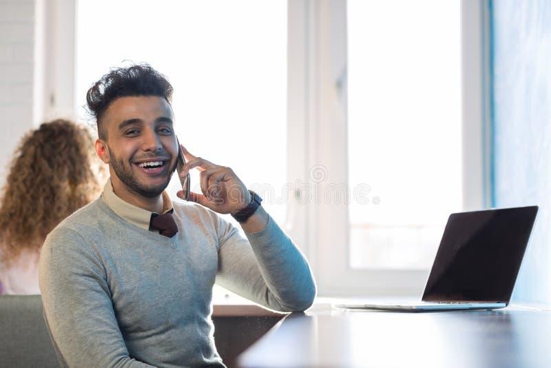 Uomo ispano di affari che parla sull'uomo d'affari In Coworking Center del computer portatile di chiamata di telefono cellulare fotografia stock
