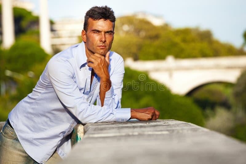 Uomo italiano serio affascinante all'aperto che si appoggia una parete Belle vecchie finestre a Roma (Italia) fotografia stock