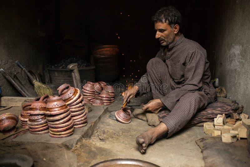 Uomo kashmiri non identificato che lavora nel fabbro a Srinagar, India immagine stock libera da diritti