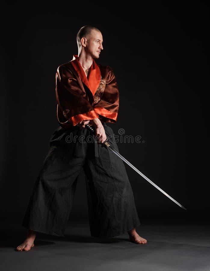 Uomo in kimono che pratica con la spada giapponese immagine stock libera da diritti