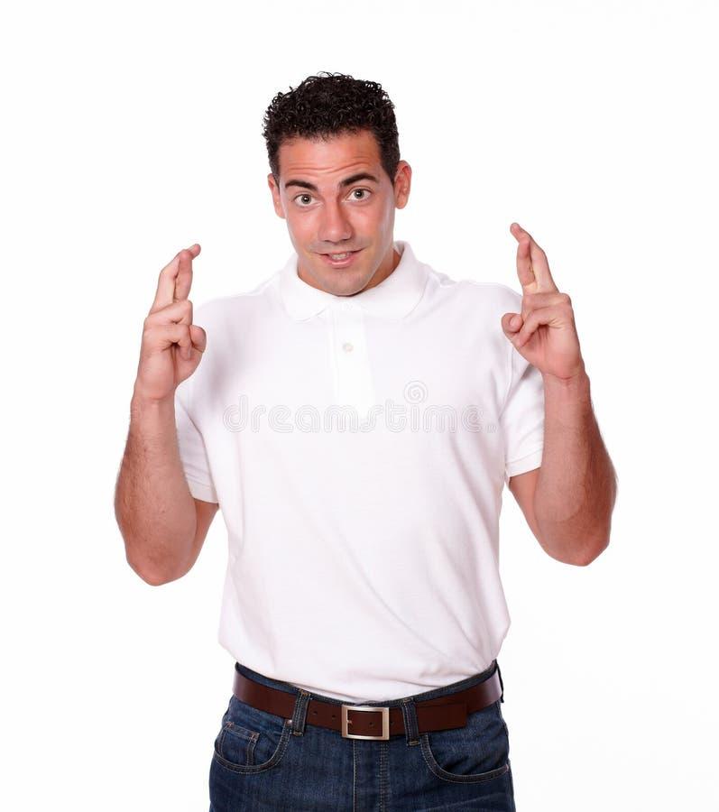 Uomo latino bello con il gesto di fortuna fotografia stock