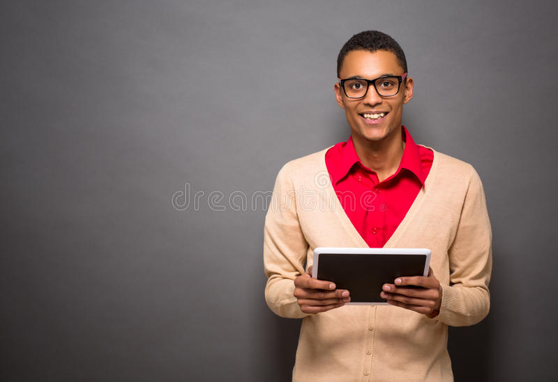 Uomo latino bello con il PC della compressa in studio immagini stock