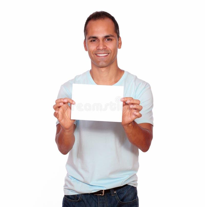Uomo latino sorridente che tiene una carta bianca fotografia stock libera da diritti
