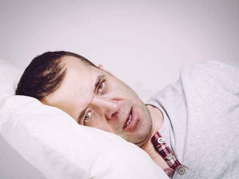Uomo a letto che si occupa dell'insonnia fotografia stock libera da diritti