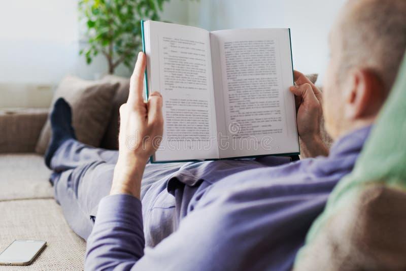 Uomo a letto legge il libro a casa fotografia stock libera da diritti