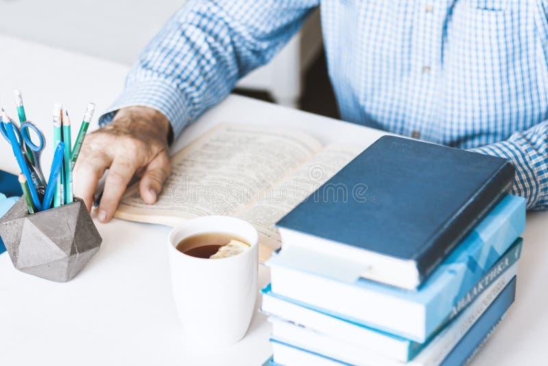 Uomo in libro di lettura blu della camicia sul posto di lavoro alla moda moderno con gli articoli per ufficio e libri, concetto d immagini stock libere da diritti