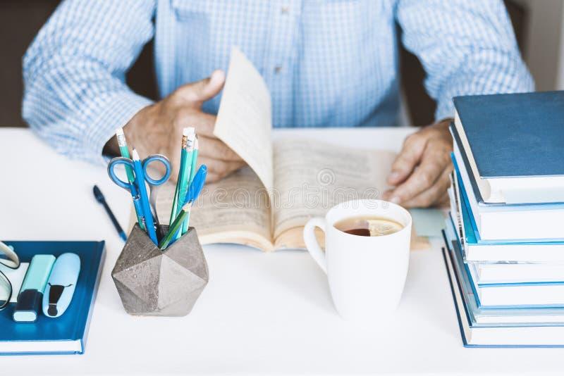 Uomo in libro di lettura blu della camicia sul posto di lavoro alla moda moderno con gli articoli per ufficio e libri, concetto d fotografia stock libera da diritti