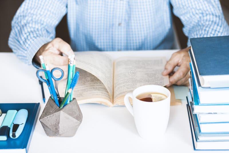 Uomo in libro di lettura blu della camicia sul posto di lavoro alla moda moderno con gli articoli per ufficio e libri, concetto d immagine stock