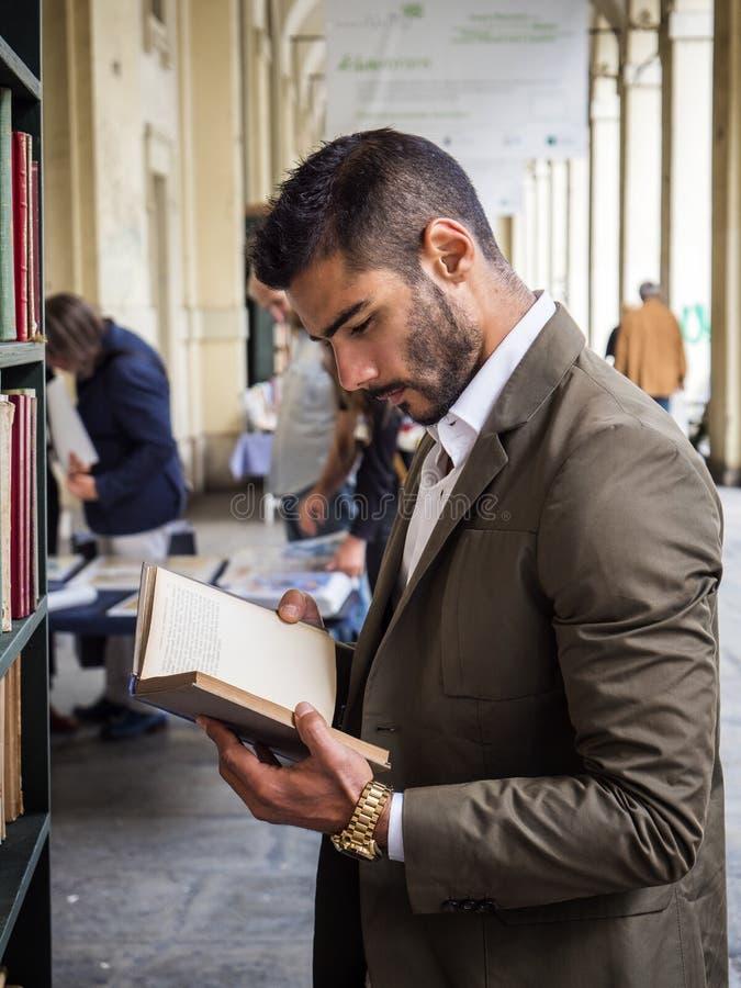 Uomo in libro di lettura del vestito fotografia stock