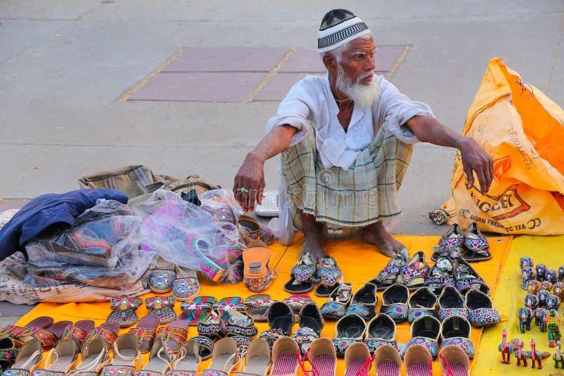 Uomo locale che vende le pantofole al mercato dall'uomo Sagar Lake a Jaipur fotografia stock libera da diritti