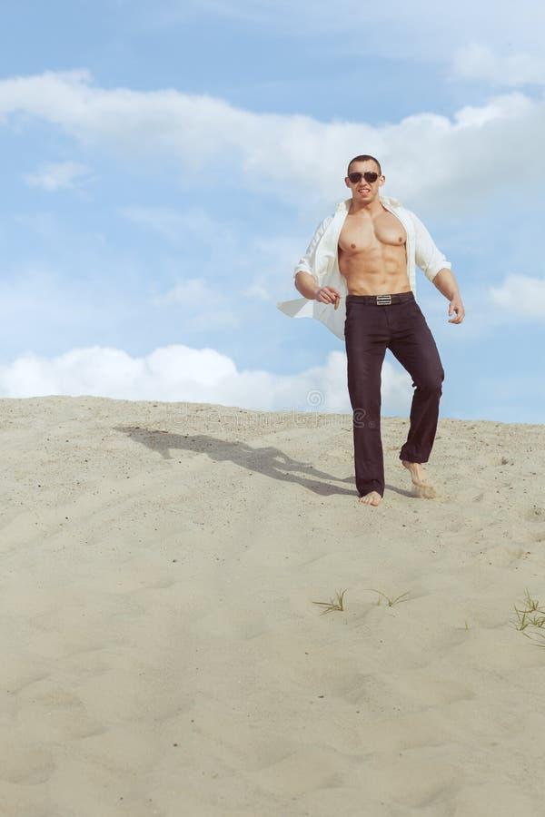 Uomo macho con i vetri e un sigaro nel deserto fotografia stock