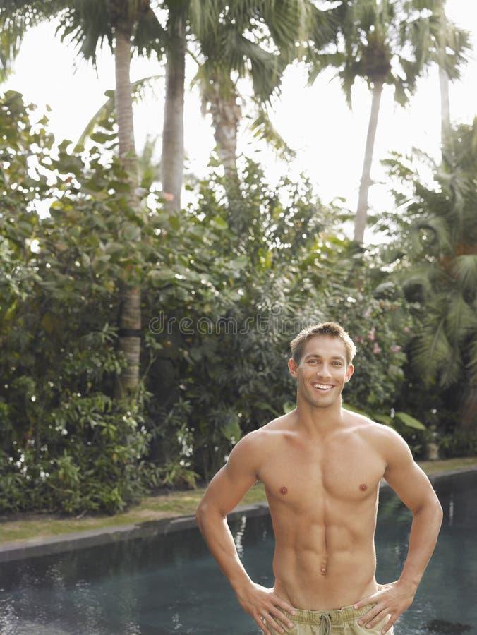Uomo macho senza camicia che sorride dalla piscina fotografia stock