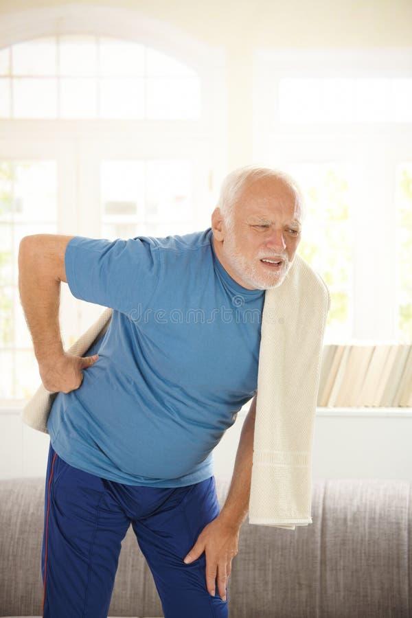 Uomo maggiore in abiti sportivi che hanno parte posteriore di dolore dentro fotografie stock libere da diritti