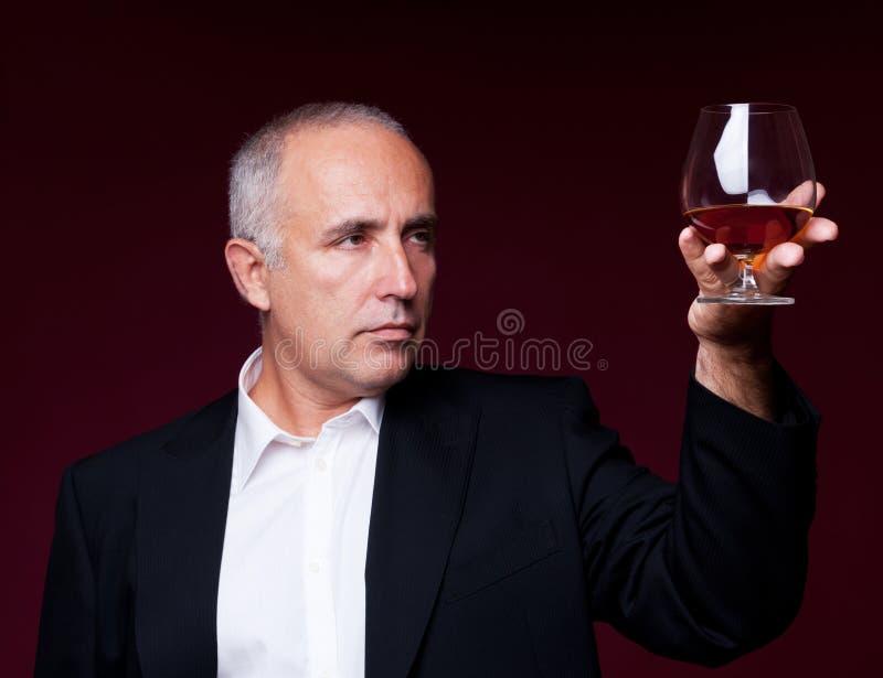 Uomo maggiore bello che tiene il vecchio vetro di brandy fotografia stock libera da diritti