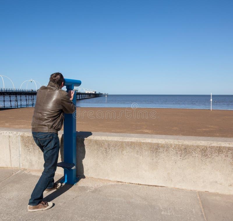 Uomo maggiore che esamina fuori sopra la spiaggia Southport fotografia stock