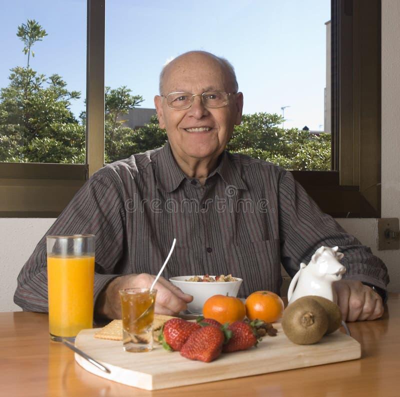 Uomo maggiore che mangia una prima colazione sana immagine stock