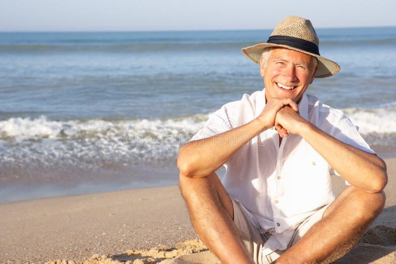 Uomo maggiore che si siede sulla distensione della spiaggia fotografie stock libere da diritti