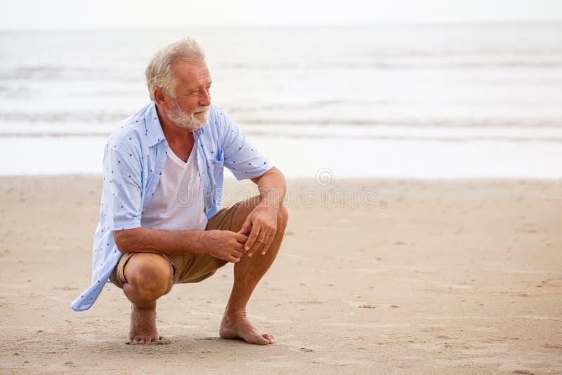 Uomo maggiore che si siede sulla distensione della spiaggia L'uomo pensionato felice si è rilassato sulla sabbia all'aperto fotografia stock libera da diritti