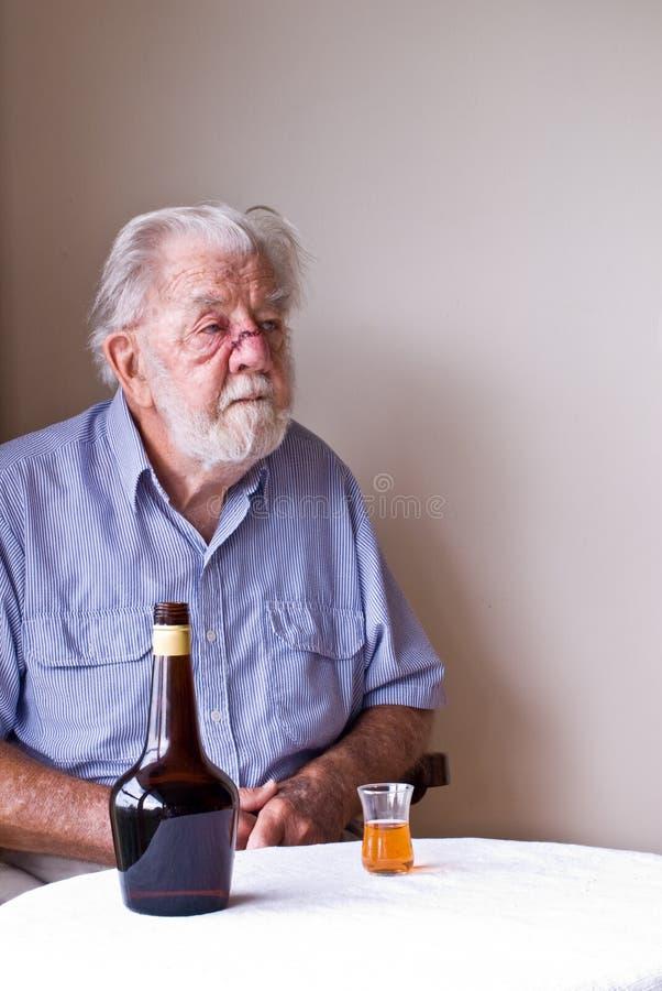 Uomo maggiore contemplativo con la bottiglia ed il vetro fotografia stock