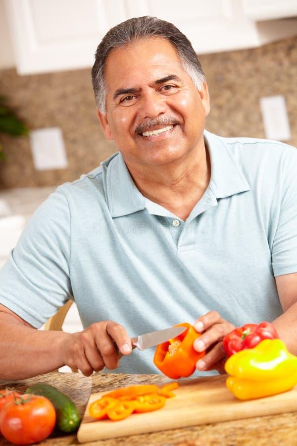 Uomo maggiore felice che taglia le verdure a pezzi fotografia stock