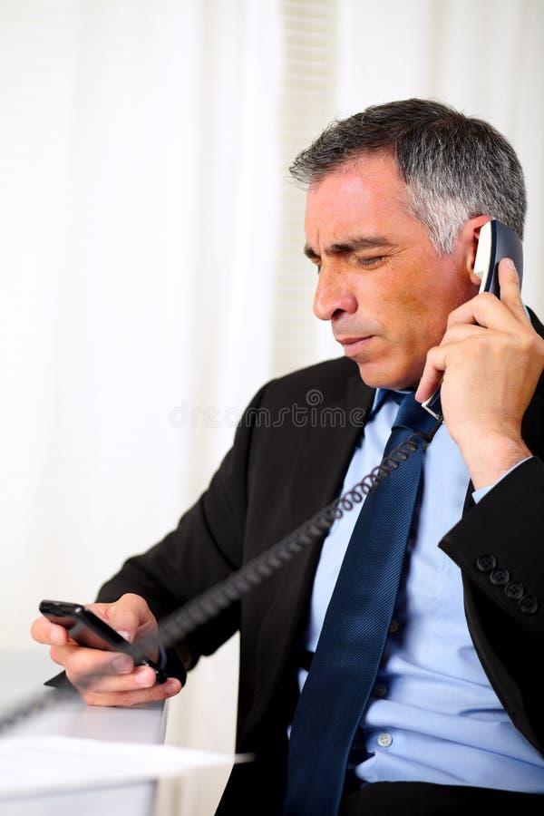 Uomo maggiore ispanico di affari che invita telefono immagine stock