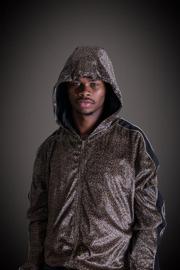 Uomo in maglia con cappuccio che esamina macchina fotografica su fondo nero fotografia stock libera da diritti