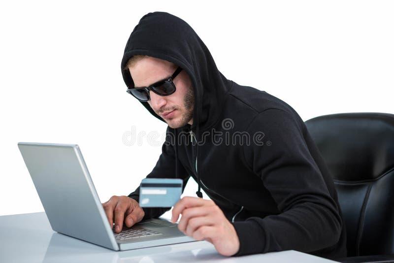 Uomo in maglia con cappuccio nera che fa spesa online immagini stock libere da diritti