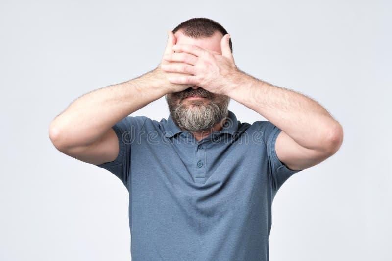Uomo in maglietta blu che copre il suo fronte di mani immagini stock libere da diritti