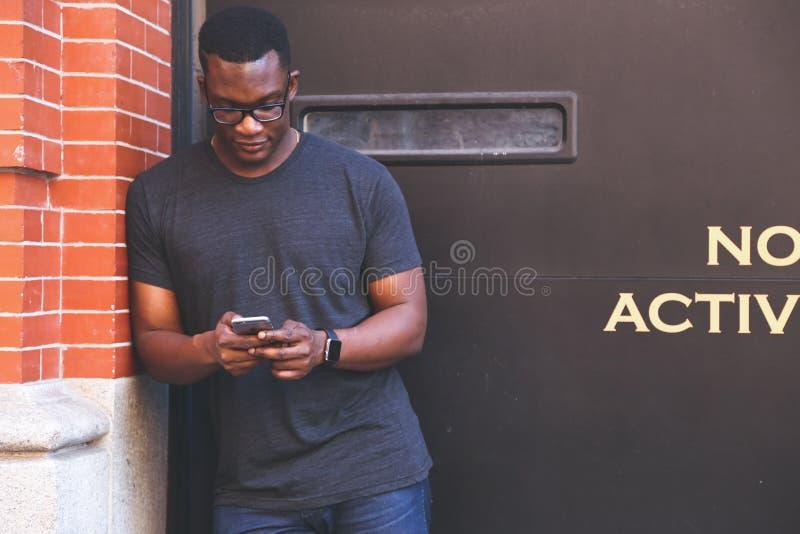 Uomo in maglietta di Grey Crew Neck che si appoggia il muro di mattoni di Brown che tiene Smartphone immagini stock libere da diritti