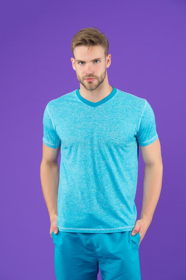 Uomo in maglietta e shorts su fondo viola Tipo in abbigliamento casual blu Macho nell'usura attiva per l'allenamento o nell'addes fotografia stock libera da diritti