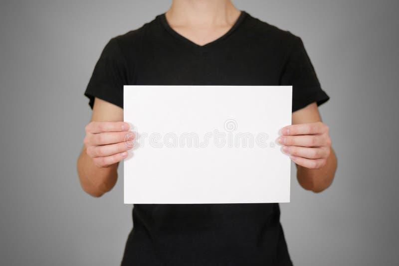 Uomo in maglietta nera che tiene la carta in bianco di bianco A4 Opuscolo prese fotografia stock libera da diritti