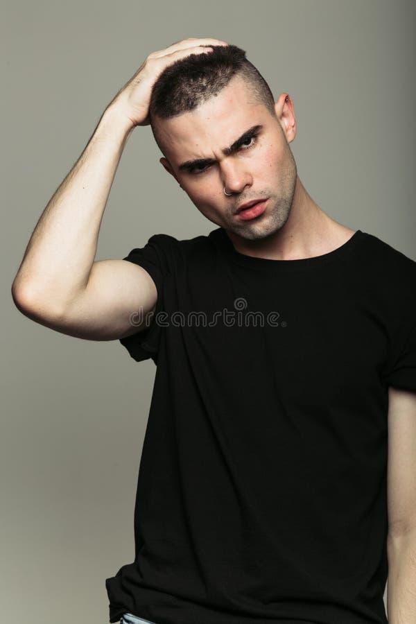 Uomo in maglietta nera che tocca i suoi capelli fotografia stock