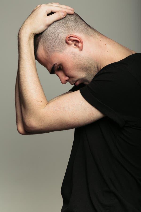 Uomo in maglietta nera con entrambe le mani sul suo testa fotografia stock libera da diritti