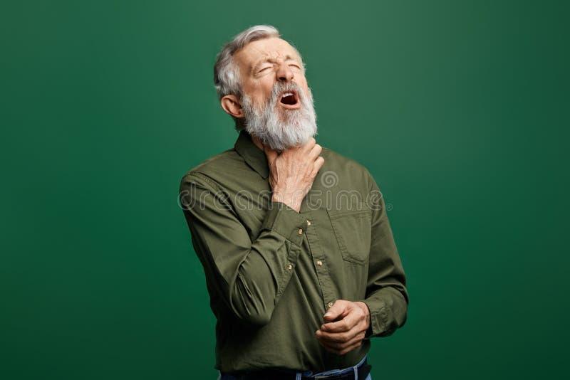 Uomo malato anziano che ha dolore della gola, tenente la sua gola fotografie stock libere da diritti
