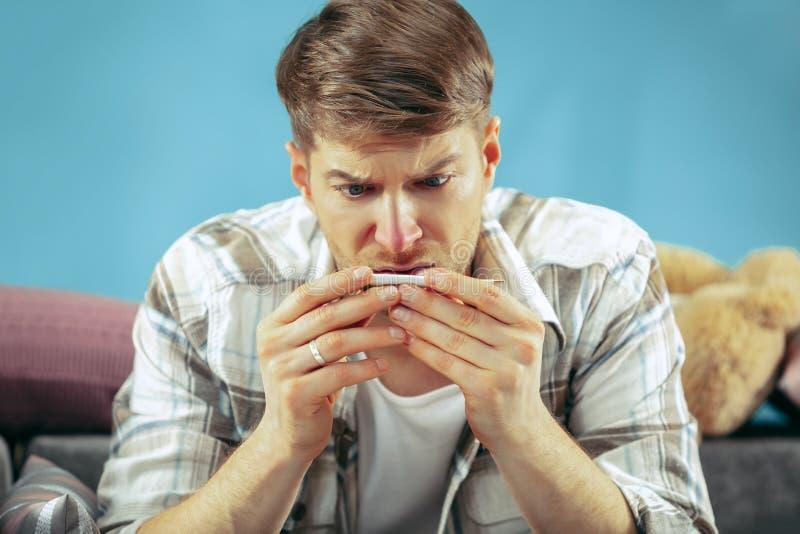 Uomo malato barbuto con il condotto di scarico che si siede sul sofà a casa Malattia, influenza, concetto di dolore Rilassamento  immagine stock libera da diritti